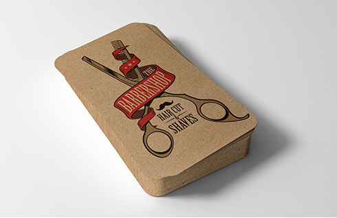 A stack of brown paper business cards for a barbershop with an vintage design
