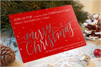 "A red Christmas party invitation featuring a message of ""Merry Christmas"". The card is featured alongside pinecones and fir tree branches."