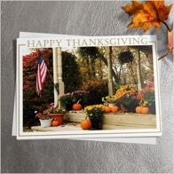 A Thanksgiving greeting card design featuring a porch covered in pumpkins and an American flag. The card is sitting on a grey background with a spotlight and a leaf accent.