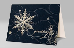 "Standing greeting card with a snowflake design that reads ""greetings"""