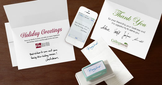 Two greeting cards, a cell phone, a signature stamp, and a check, which has been stamped with the signature stamp, all on a wooden background
