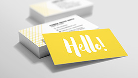 "A stack of business cards featuring a yellow design with the word ""Hello!"" on the back."