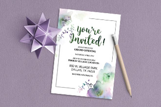 'You're invited!' is written in a green font against a white background on the front of this invitation. Watercolor floral patterns and a black border complete the look.