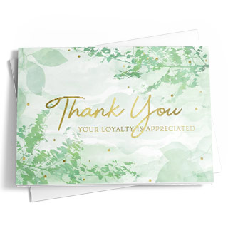 A thank you card with a white and green design featuring watercolor tree branches. The greeting card is on top of a white envelope on a white background.