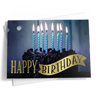 A birthday card featuring a dark chocolate cake and lit blue candles. The message reads 'Happy Birthday' in gold.