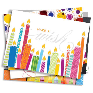 A stack of birthday cards. The one on top features a multi-color assortment of illustrated candles with the message 'make a wish'.