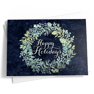 This dark blue card with hints of starlight features a beautiful wreath and text in teal, beige, and white. The text reads 'Happy Holidays.'