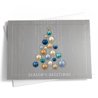 'Season's Greetings' is written in white text within a gray and white border – presented against a gray woodgrain background. Ornamental accents are presented on the front of the card in tones of blue, green, white, silver, and gold. The opposing side of the greeting is the same gray woodgrain as the front and the solid white interior provides the ideal space to include a custom message, your digital signature, and company logo.