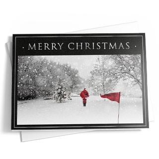 This Christmas card features black and silver borders around a snow-covered golf course; Santa walks off the final hole in his red suit that complements a red golf flag. The message reads 'Merry Christmas' at the top in silver letters.;