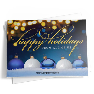 This golf-themed holiday card features blue and white golf ball ornaments on the front. The five ornaments lie in the snow at the bottom of the card. The front and back of the card include a dark blue background with a bokeh design in gold, white, and blue. The message on the front reads 'Happy Holidays From All Of Us' in gold and white. Add personalized text below.